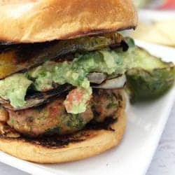 Closeup showing grilled burger with a heaping serving of guacamole on top.