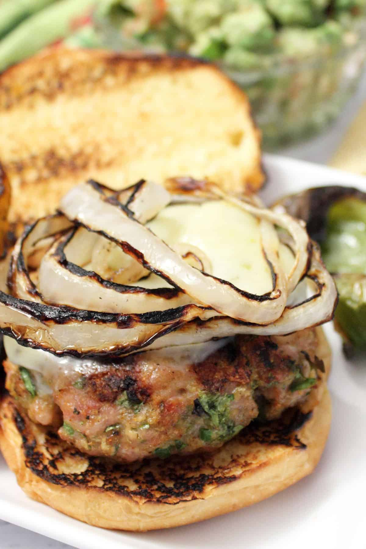 Closeup of burger on a toasted roll with topping of grilled onions.
