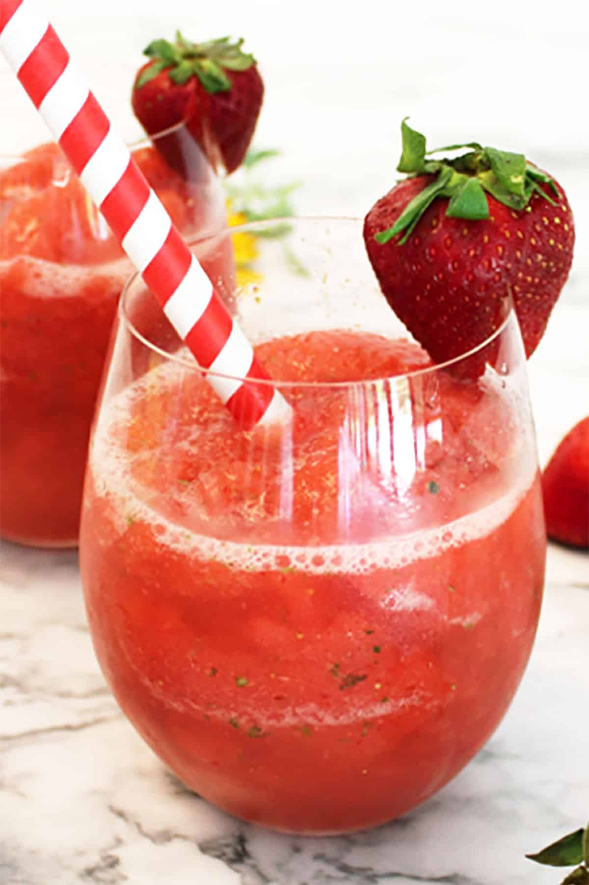 Closeup of strawberry mule with strawberry garnish and red and white straw.