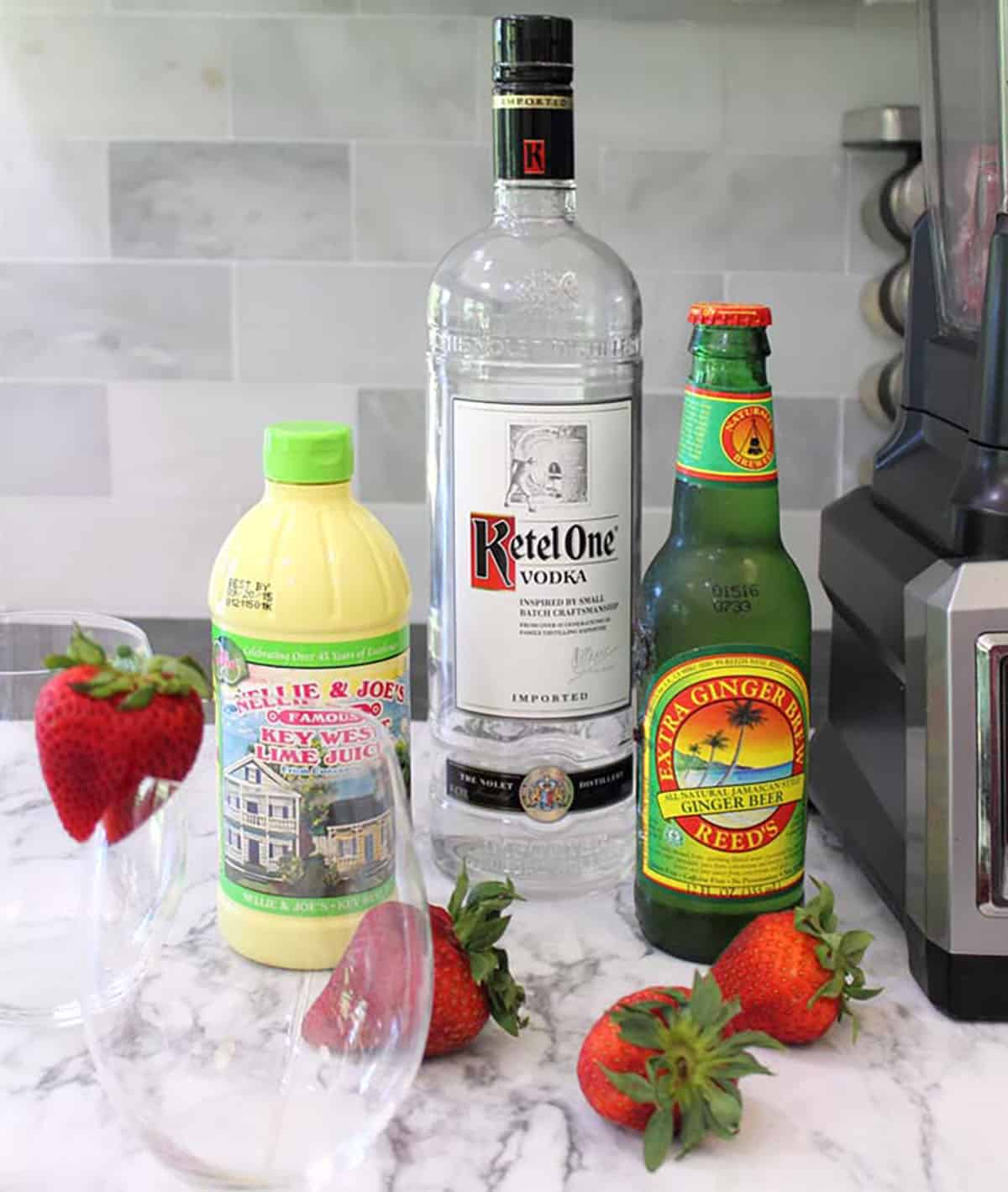 Moscow Mule ingredients - vodka, lime juice, strawberries, ginger beer on white table.