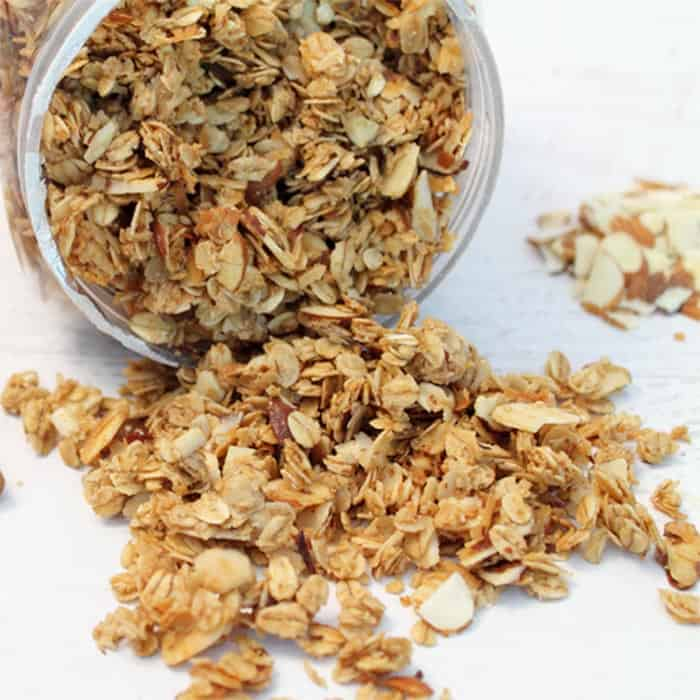 Granola spilling out of container showing crunchy oats, nuts and coconut.