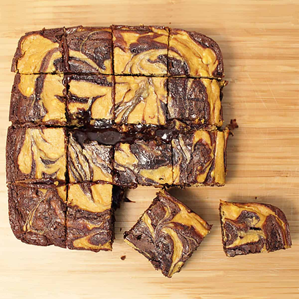 Overhead of brownies cut into bars on wooden cutting board.
