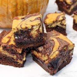 Stacked pumpkin cheesecake brownies on white table in front of pumpkin.