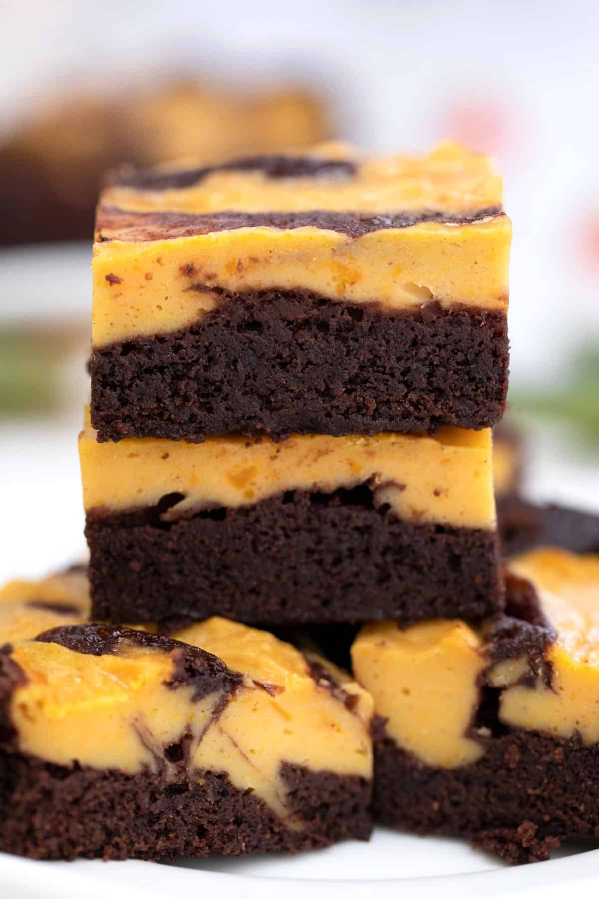 Stacked brownies showing layer of brownies and layer of pumpkin cheesecake.
