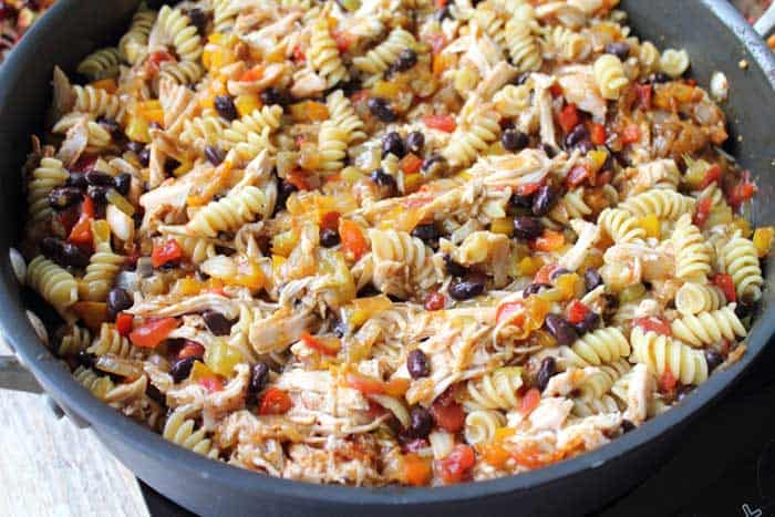 Simmered chicken, black beans, tomatoes and pasta in skillet.