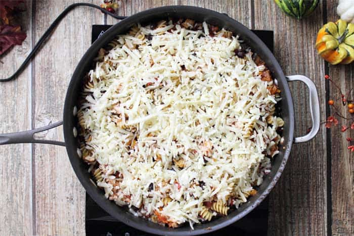 overhead of taco pasta in skillet sprinkled with cheese