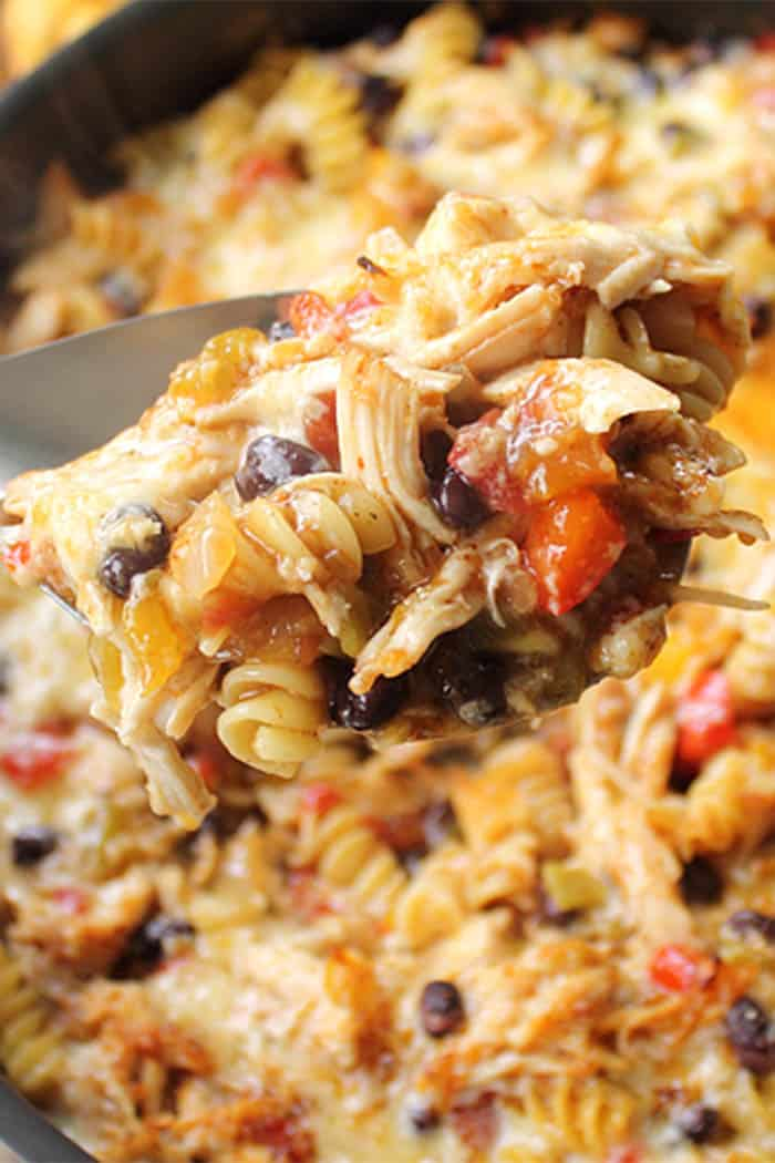 Closeup of spoonful of chicken, pasta, tomatoes and black beans above skillet.
