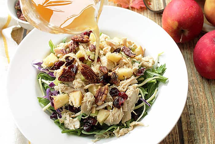 Pouring apple cider vinaigrette over apple chicken salad.