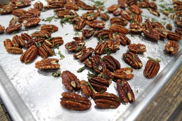 Closeup of roasted rosemary pecans on cookie sheet.
