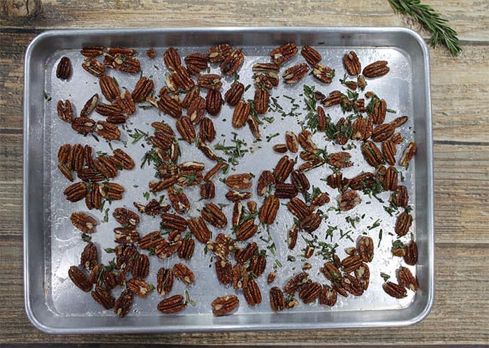 Pecans and rosemary are sprinkled on a large cookie sheet.