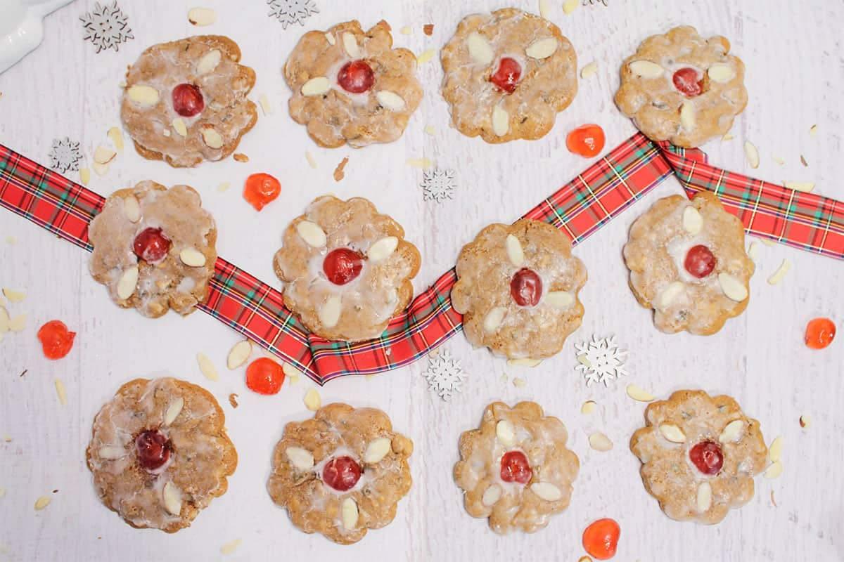 Cookies in grid pattern on white table with plaid ribbon beneath them.