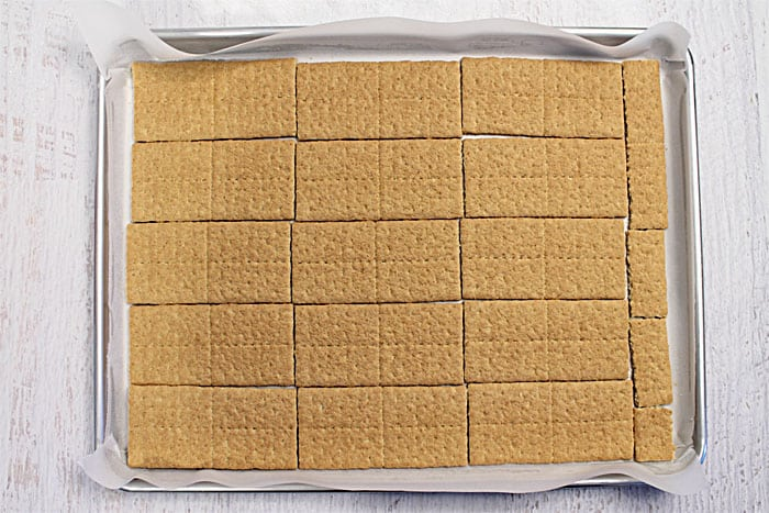 Laying out the graham crackers on a cookie sheet.