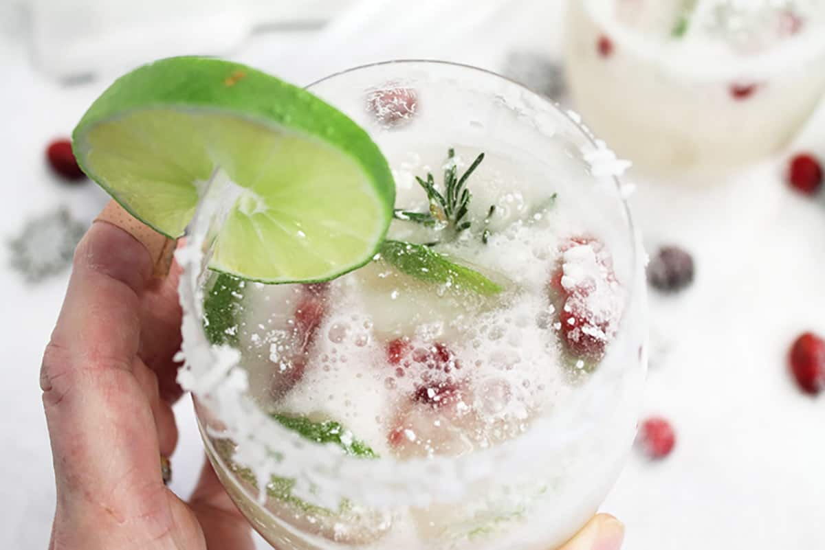 Closeup holding white christmas margarita to see coconut rim and holiday ice cubes.