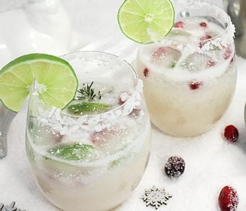 Closeup of two white christmas margaritas with lime wedge and sugared cranberries around them.