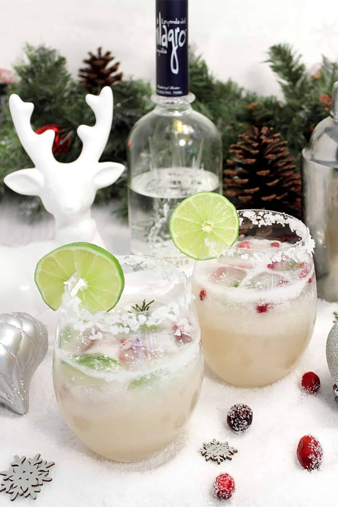 Two margaritas with lime wedge on white table with deer in background.