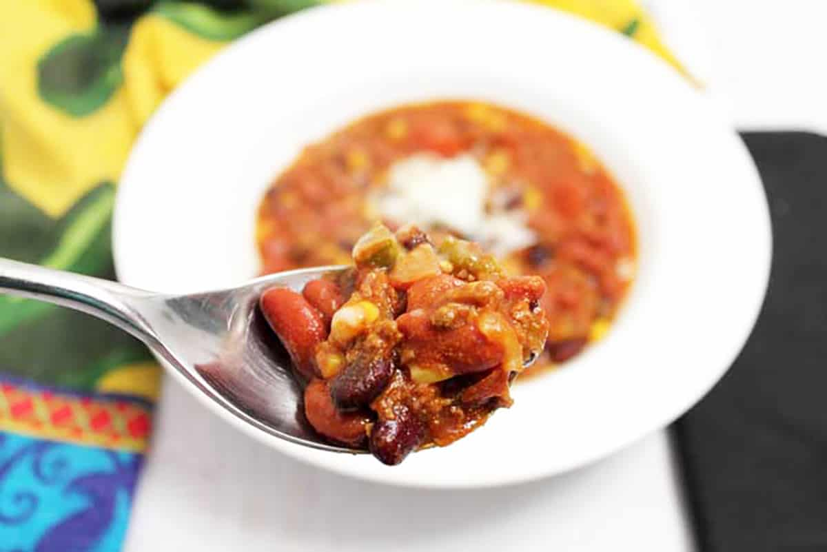 Closeup of bite of chili on spoon showing beans and seasoned beef in broth.