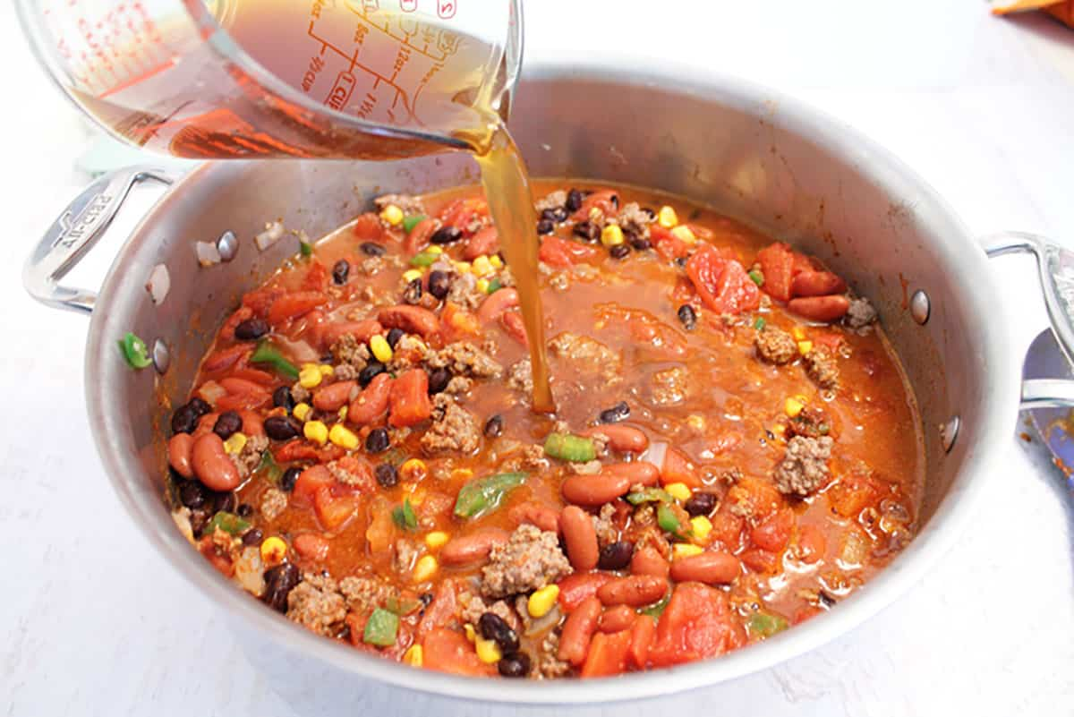 Pouring beef stock into chili mixture in large stock pot.