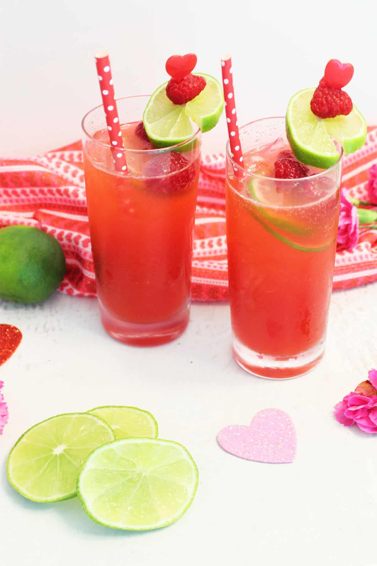 Two drinks with straws with Valentines Day towel flowers and lime slices.