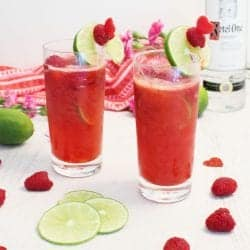 Two raspberry lime rickey cocktails with garnish on white table with raspberries and lime slices by them.