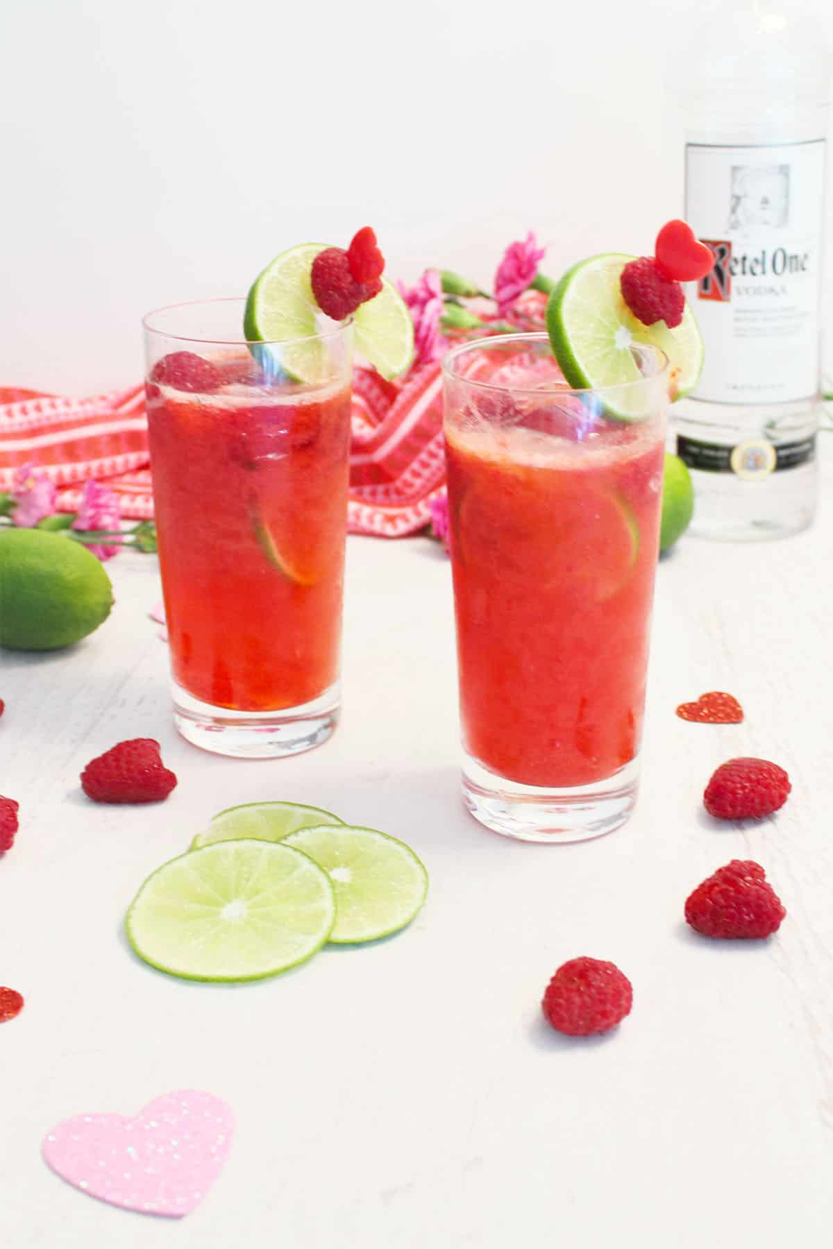 Two raspberry lime rickey cocktails with garnish on white table with raspberries, lime slices and vodka bottle.