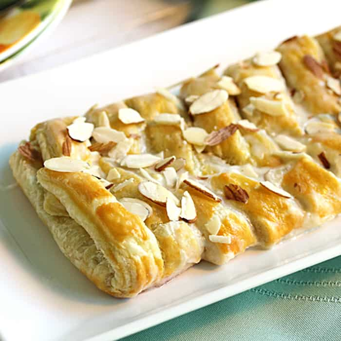 Showing baked almond breakfast danish on white plate.