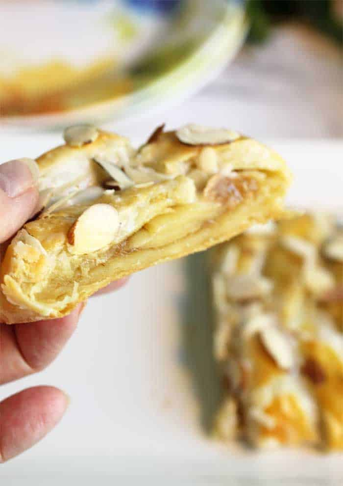Holding slice of pastry to show filling.