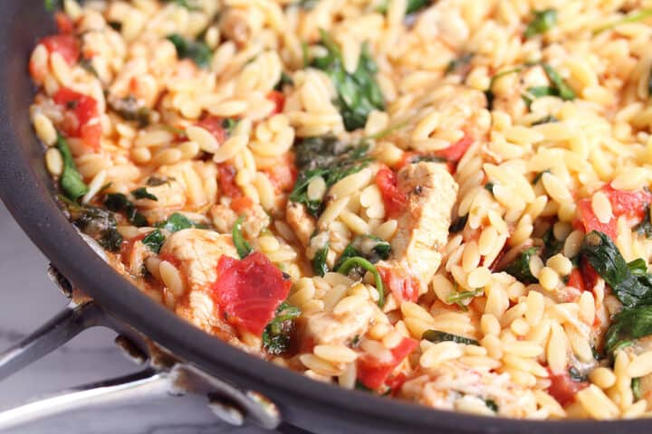 Closeup of orzo and chicken in pan.