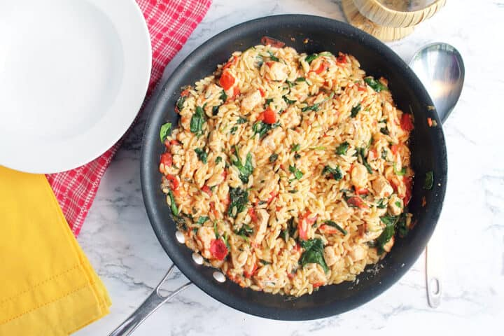 Pan of chicken and orzo skillet on table ready to serve.