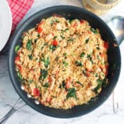 Skillet of chicken and orzo on marble table ready to serve.