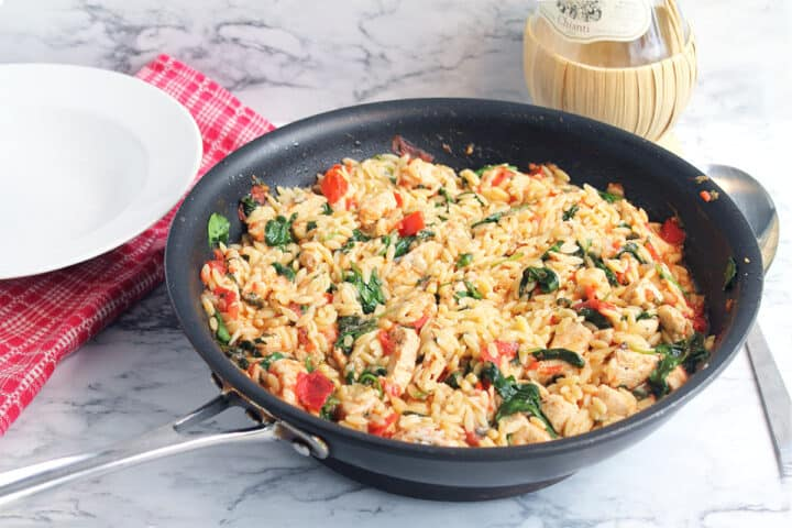 Skillet of chicken orzo near wine bottle and serving bowl.