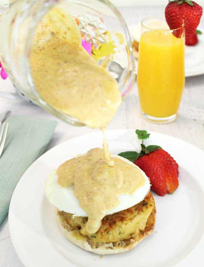 Crab Cake Eggs Benedict pouring Hollandaise | 2 Cookin Mamas