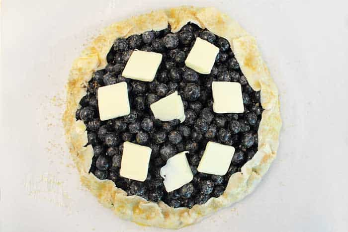 Easy Rustic Blueberry Galette dot with butter | 2 Cookin Mamas