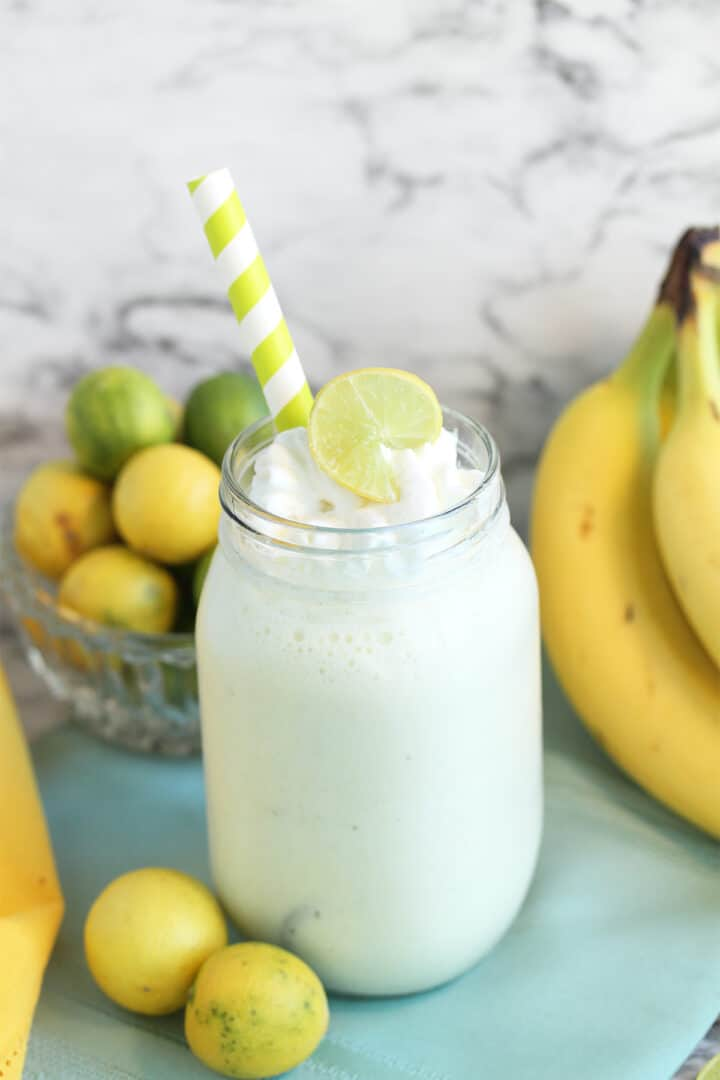Key Lime Smoothie in mason jar with lime slice garnish and key limes and bananas behind it.