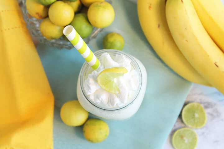 Overhead of smoothie garnished with whipped cream topping beside bananas and limes.