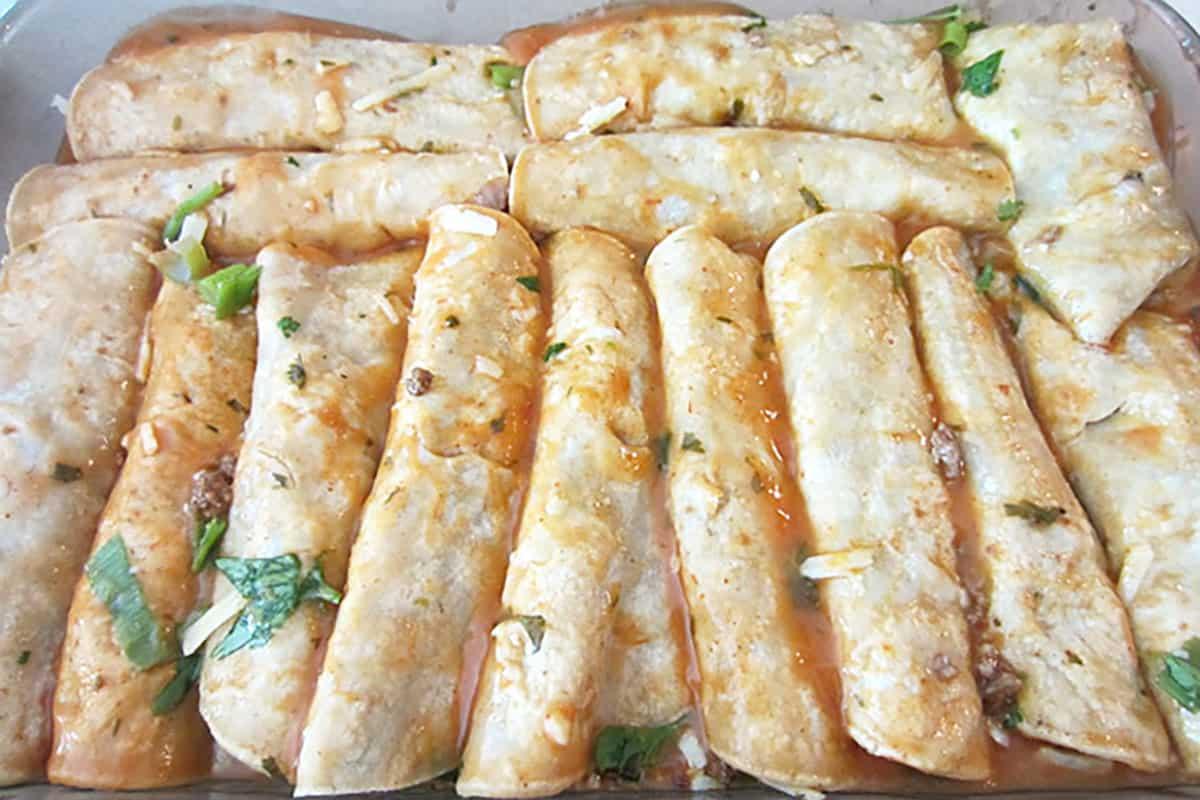 Rolled enchiladas in baking dish.