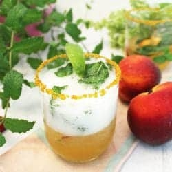 Bubbling Peach Mint Julep with gold sugar rim on peach napkin.