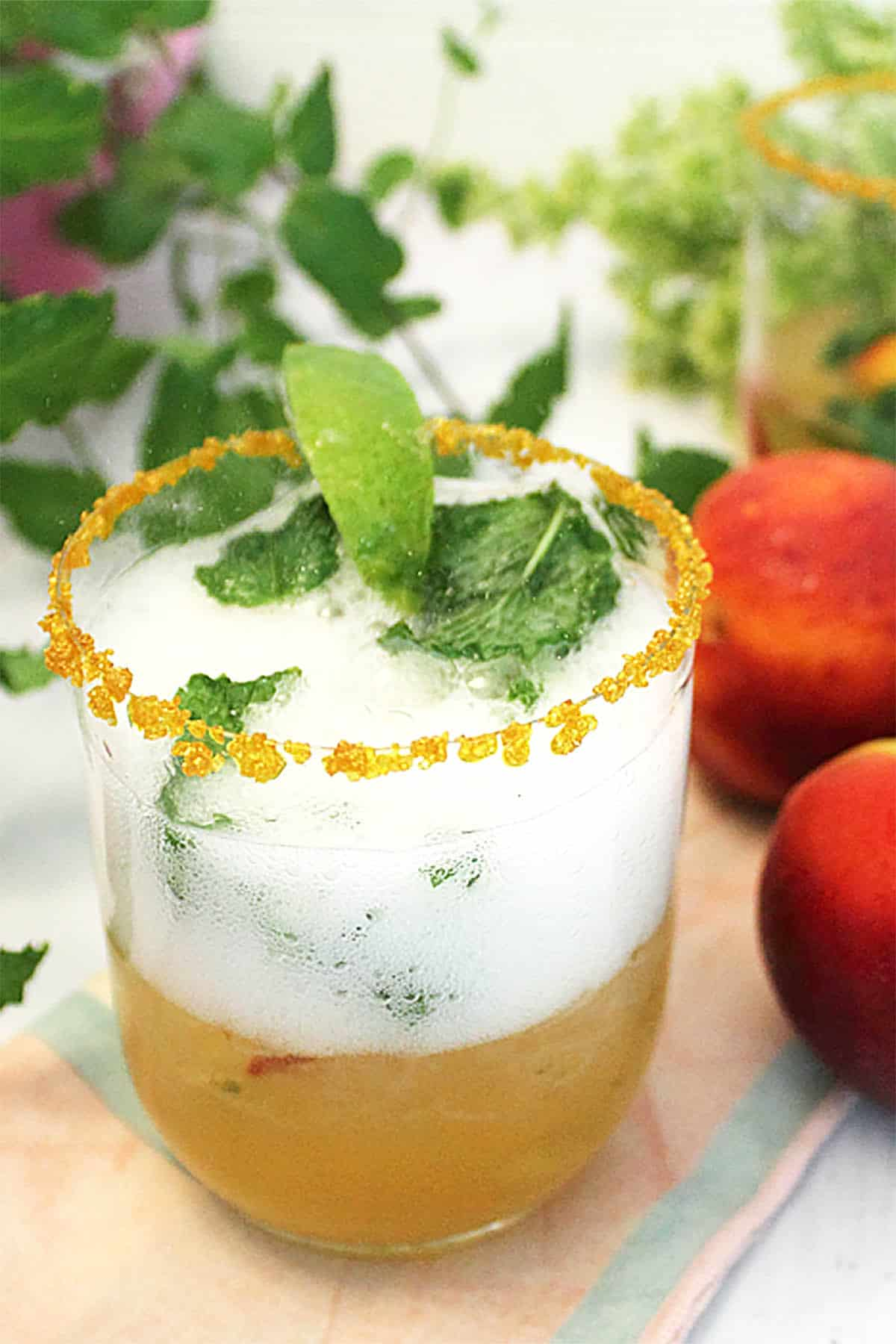 Mint Julep in glass with gold sugar rim with peaches beside it.