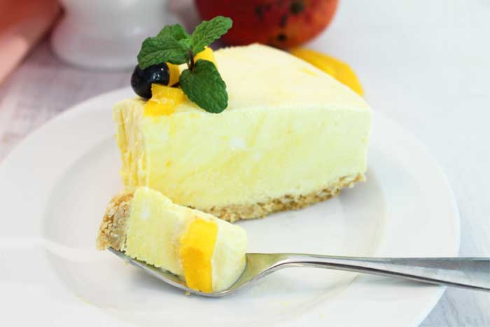 Mango Pineapple Icebox Cheesecake slice with bite