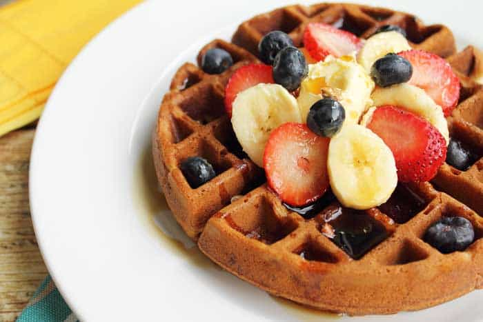Closeup of full waffle showing crispy brown outside and garnishes of fruit.