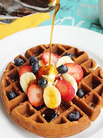 Pouring syrup over Banana Bread Waffles topped with sliced fruit.