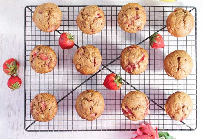 Baked muffins out of muffin tin, cooling on rack with strawberries scattered around.