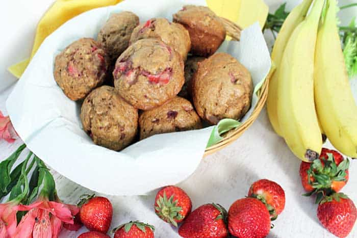 Overhead of Banana Strawberry Muffins in basket with bananas, strawberries and flowers beside it.