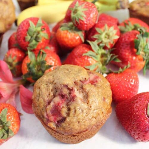Single muffin surrounded by strawberries.