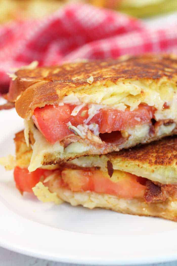 Closeup shot of inside of sandwich showing browned bread, oozing cheese and tomato.