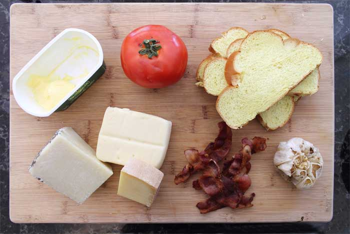 Ingredients for sandwich on wooden cutting board including roasted garlic and bacon.