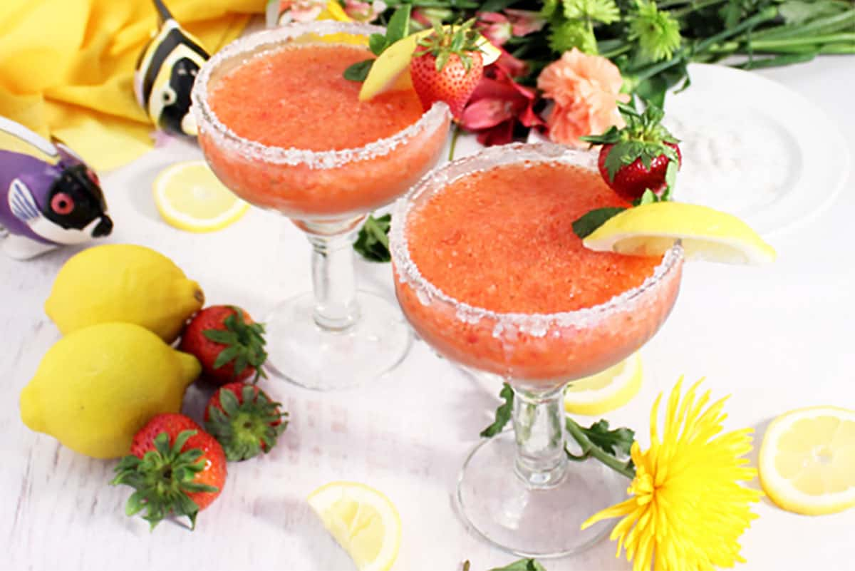2 frozen margaritas with lemon and strawberry garnish on white table with fruit and flowers scattered around.