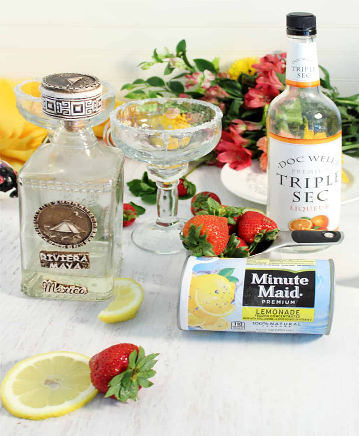 Ingredients for margarita on white table with flowers in background.