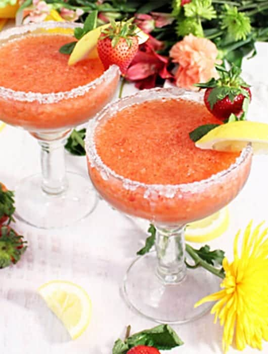 2 strawberry margaritas on white table with flowers and fruit around base.