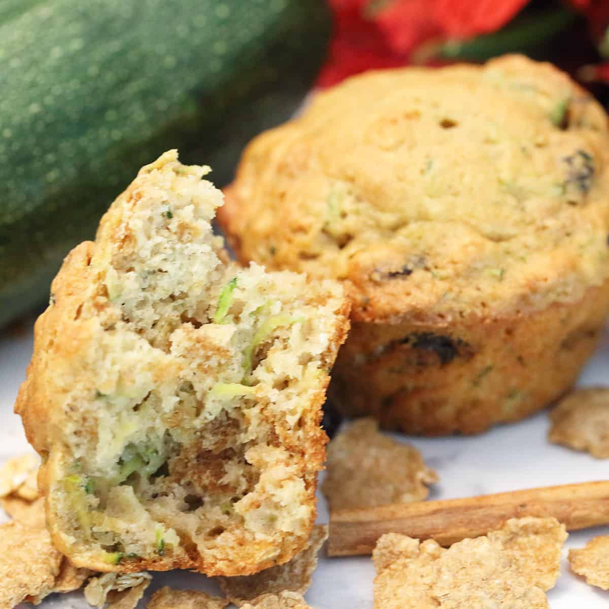 Bite of muffin on white table with zucchini in back.
