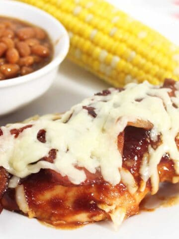 Closeup of bbq chicken on white plate with corn and baked beans.